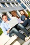 Raparigas ao ar livre e homem com portátil Fotografia de Stock