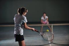 Raparigas que jogam o jogo do tênis interno Imagens de Stock Royalty Free