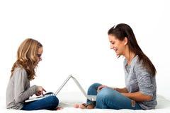 Raparigas que trabalham em portáteis Imagem de Stock Royalty Free