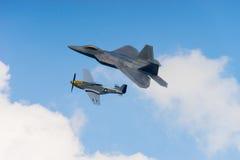 Rapaz F-22 y mustango p51 en las nubes Imagen de archivo