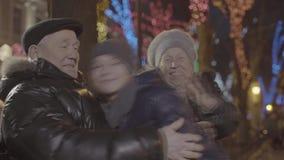 Rapaz pequeno acolhedor do neto do parque da noite da família que corre sobre à avó que abraça na iluminação festiva da luz de Na vídeos de arquivo