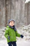 Rapaz pequeno adorável, flocos de neve de sopro fora em um dia nevado Fotografia de Stock