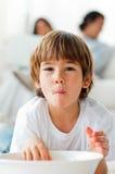 Rapaz pequeno adorável que come microplaquetas no assoalho Imagens de Stock Royalty Free