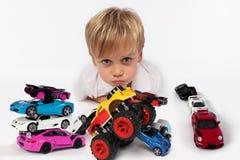 Rapaz pequeno adorável que encontra-se cercado toda por brinquedos do carro com seus mordentes e bordos bonitos prontos para beij fotografia de stock