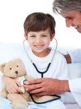 Rapaz pequeno adorável que joga com seu doutor Fotografia de Stock Royalty Free