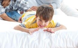 Rapaz pequeno adorável que joga com seus pais Imagem de Stock