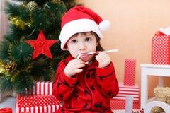 Rapaz pequeno agradável no chapéu de Santa com pirulito Imagem de Stock Royalty Free