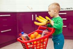 Rapaz pequeno alegre com carrinho de compras O rapaz pequeno toma bananas Compra, desconto, conceito da venda foto de stock royalty free