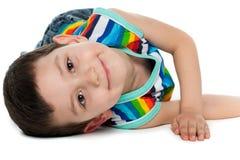 Rapaz pequeno alegre no assoalho Fotografia de Stock