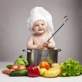 Rapaz pequeno alegre no chapéu do cozinheiro chefe Imagens de Stock