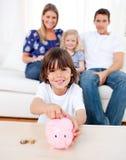 Rapaz pequeno alegre que introduz a moeda em um piggybank imagem de stock