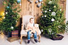 Rapaz pequeno alegre que joga com seu brinquedo pela árvore de Natal imagem de stock royalty free