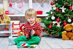 Rapaz pequeno alegre que joga com seu carro vermelho do brinquedo Imagens de Stock