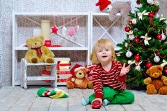 Rapaz pequeno alegre que joga com seu carro vermelho do brinquedo Imagens de Stock Royalty Free