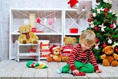 Rapaz pequeno alegre que joga com seu carro vermelho do brinquedo Imagem de Stock Royalty Free