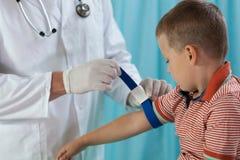 Rapaz pequeno antes de tomar a amostra de sangue Fotografia de Stock Royalty Free