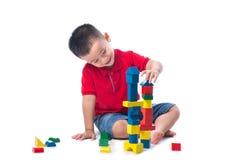 Rapaz pequeno asiático que joga com os blocos coloridos, isolados no branco Imagem de Stock Royalty Free