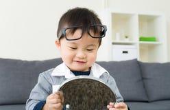 Rapaz pequeno asiático que usa o espelho fotografia de stock