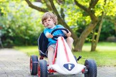 Rapaz pequeno ativo que tem o divertimento e que conduz o carro do brinquedo fotos de stock royalty free