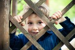 Rapaz pequeno atrás da cerca imagem de stock royalty free