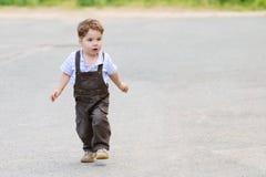 Rapaz pequeno bonito bonito no terno marrom, caminhadas foto de stock royalty free