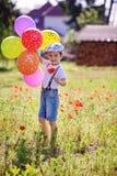 Rapaz pequeno bonito com a flor da papoila no campo da papoila com balões fotos de stock royalty free