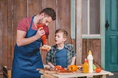 Rapaz pequeno bonito com o pai no avental que prepara o cachorro quente junto no quintal fotografia de stock