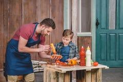 Rapaz pequeno bonito com o pai no avental que prepara o cachorro quente junto no quintal imagens de stock royalty free