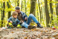 Rapaz pequeno bonito com seu pai durante a caminhada no pai da floresta que joga com filho pequeno em um piquenique no parque den imagem de stock royalty free