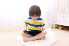 Rapaz pequeno bonito com tablet pc Fotografia de Stock Royalty Free