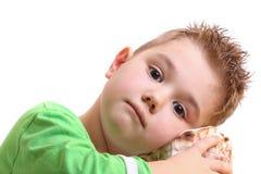 Rapaz pequeno bonito com um escudo do mar Imagens de Stock