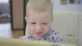 Rapaz pequeno bonito, comendo o papa de aveia para o caf? da manh? em casa, ao olhar desenhos animados na tabuleta Crian?as e tec vídeos de arquivo