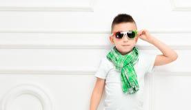 Rapaz pequeno bonito da forma em calças e t-shirt e lenço brilhantes imagens de stock
