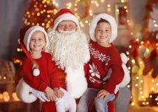 Rapaz pequeno bonito e menina com Santa Claus na sala Fotografia de Stock