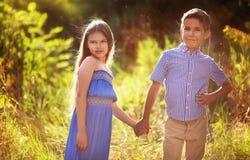 Rapaz pequeno bonito e menina que guardam as mãos no parque Imagem de Stock Royalty Free