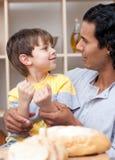 Rapaz pequeno bonito e seu pão da estaca do pai Foto de Stock
