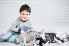 Rapaz pequeno bonito e três cachorrinhos roncos novos que dormem em um fundo branco Símbolo do ano novo 2018 fotos de stock royalty free