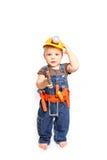 Rapaz pequeno bonito em um capacete alaranjado e ferramentas em um backgro branco Imagens de Stock