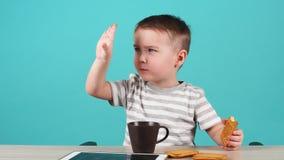 Rapaz pequeno bonito em um humor alegre que senta-se na tabela e que levanta para a câmera