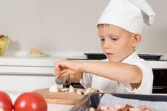 Rapaz pequeno bonito em um toque dos cozinheiros chefe que corta cogumelos Imagem de Stock