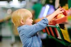 Rapaz pequeno bonito em uma despensa ou em um supermercado que escolhem a romã orgânica fresca imagens de stock