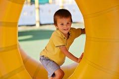 Rapaz pequeno bonito, jogando em um anel plástico do cilindro do rolamento, ful Imagens de Stock