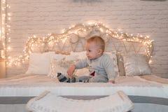 Rapaz pequeno bonito na cama Fundo das luzes de Cristmas imagens de stock