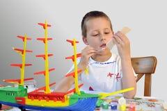 Rapaz pequeno bonito, navio do woodcraft, pintando Fotografia de Stock