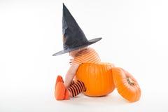 Rapaz pequeno bonito no chapéu da bruxa que senta-se dentro da abóbora grande fotografia de stock royalty free