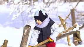 Rapaz pequeno bonito no parque do inverno Senta-se em uma cerca de madeira e em jogos com uma vara video estoque