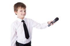 Rapaz pequeno bonito no terno de negócio com o microfone que toma o intervie Foto de Stock Royalty Free