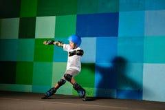Rapaz pequeno bonito nos patins de rolo que correm contra a parede azul dos grafittis imagem de stock royalty free