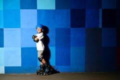 Rapaz pequeno bonito nos patins de rolo que estão contra a parede azul dos grafittis imagem de stock