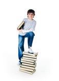 Rapaz pequeno bonito perto da pilha de livros grandes Fotografia de Stock